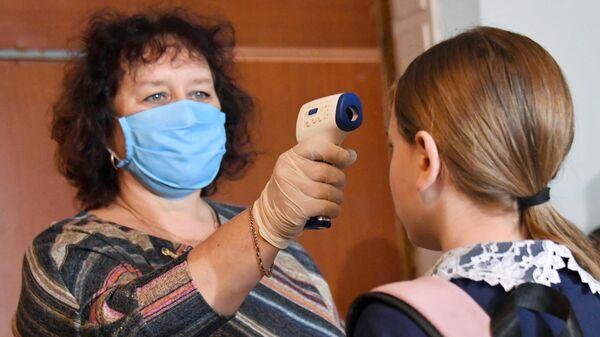 Учитель измеряет температуры ученикам при входе в общеобразовательную школу