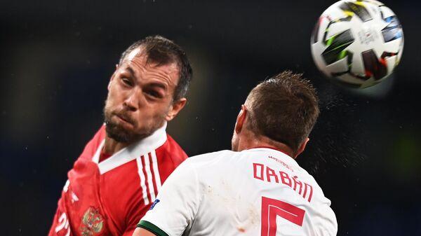 Нападающий сборной России Артем Дзюба (слева) и защитник сборной Венгрии Вилли Орбан