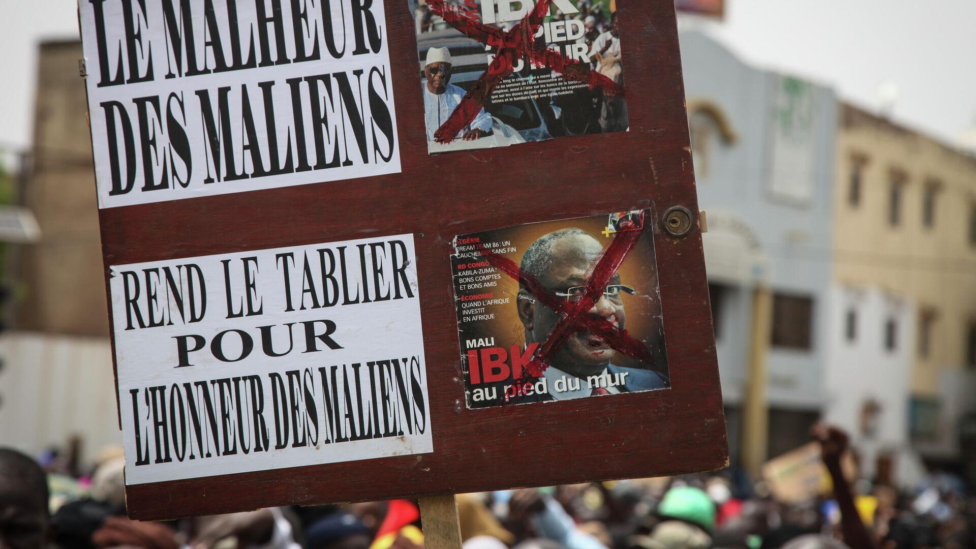 Участники акции протеста в Мали держат плакат с надписью Беда малийцев. Уступите во имя чести малийцев  - РИА Новости, 1920, 20.07.2021