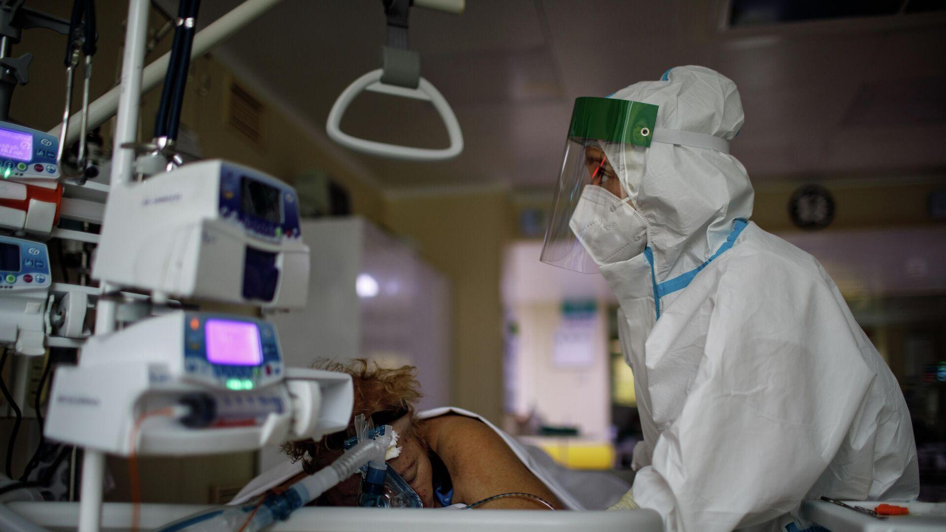 Медицинский работник оказывает помощь пациенту с COVID-19 в отделении реанимации и интенсивной терапии городской клинической больницы № 52 - РИА Новости, 1920, 16.10.2020