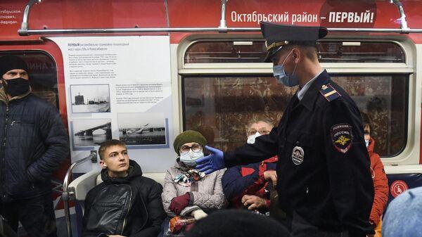Сотрудник правоохранительных органов и пассажир без маски во время рейда по проверке соблюдения масочного режима на станции метро Красный проспект в Новосибирске