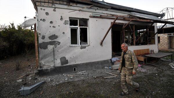 Местный житель у жилого дома, пострадавшего в результате обстрела села Бахарлы Агдамского района