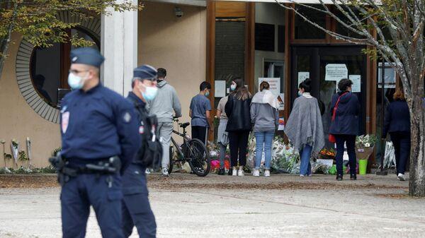 Люди несут цветы к месту, где было совершено нападение на учителя в коммуне Конфлан-Сент-Онорин, Франция