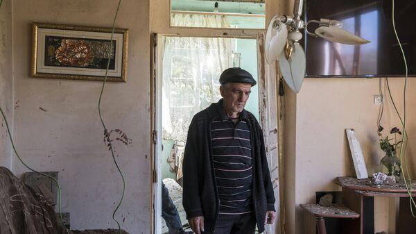 Мужчина в своем доме, поврежденном в результате ракетного обстрела селения Шош