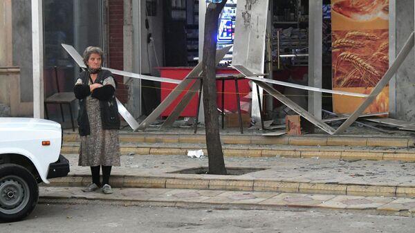 Женщина возле разбитых витрин магазина в результате ракетного обстрела города Гянджа