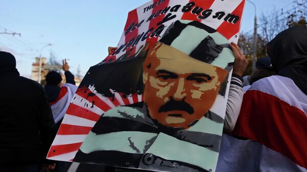 Демонстрант несет плакат с изображением президента Беларуси Александра Лукашенко во время митинга оппозиции в Минске