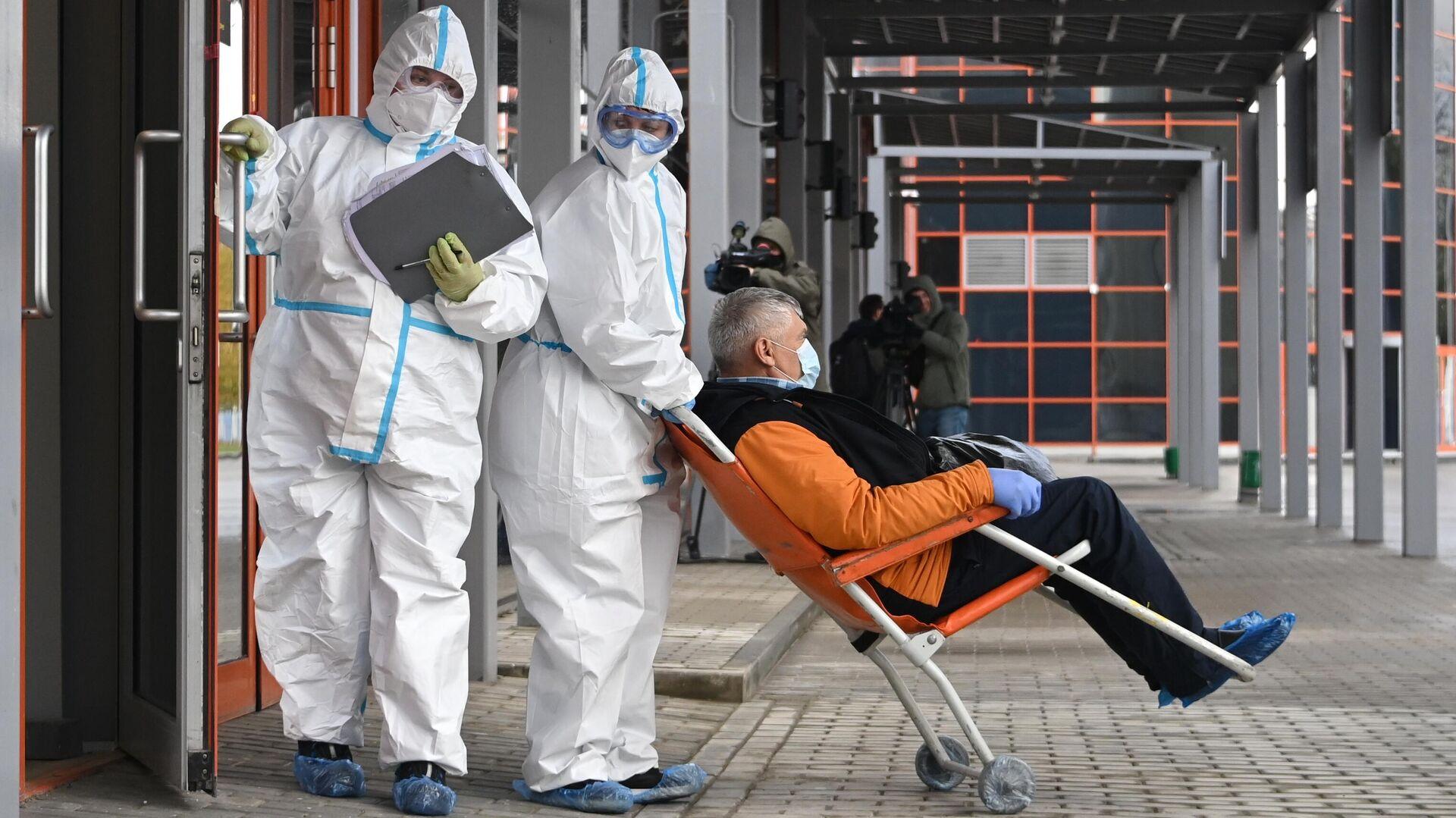 Сотрудники скорой помощи доставляют пациента во временный госпиталь COVID-19 на ВДНХ - РИА Новости, 1920, 05.11.2020
