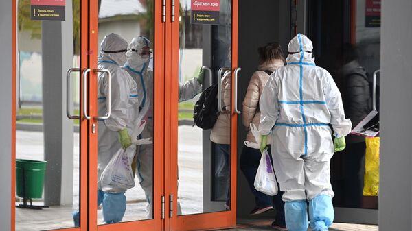 Сотрудники скорой помощи доставляют пациента во временный госпиталь COVID-19 на ВДНХ в Москве