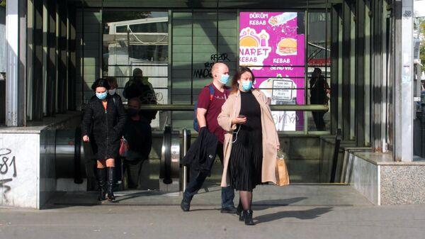 Прохожие в медицинских масках недалеко от торгового центра Аркады Панкрац в Праге