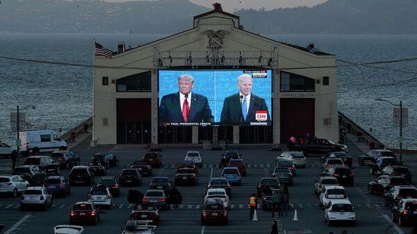 Люди смотрят трансляцию дебатов между президентом США Дональдом Трампом и кандидатом в президенты Джо Байденом