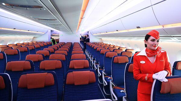 Стюардесса в салоне дальнемагистрального широкофюзеляжного пассажирского самолета Airbus A350-900