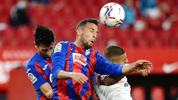 Eibar's Argentinian defender Esteban Burgos (C) jumps for the ball with Eibar's Portuguese defender Paulo Oliveira (L) and Sevilla's Brazilian defender Diego Carlos during the Spanish League football match between Sevilla and Eibar at the Sanchez Pizjuan stadium in Sevilla on October 24, 2020. (Photo by CRISTINA QUICLER / AFP)