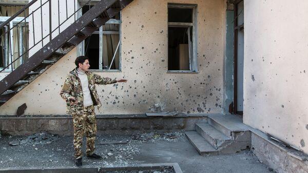 Мужчина возле своего дома, поврежденного в результате обстрела города Аскеран