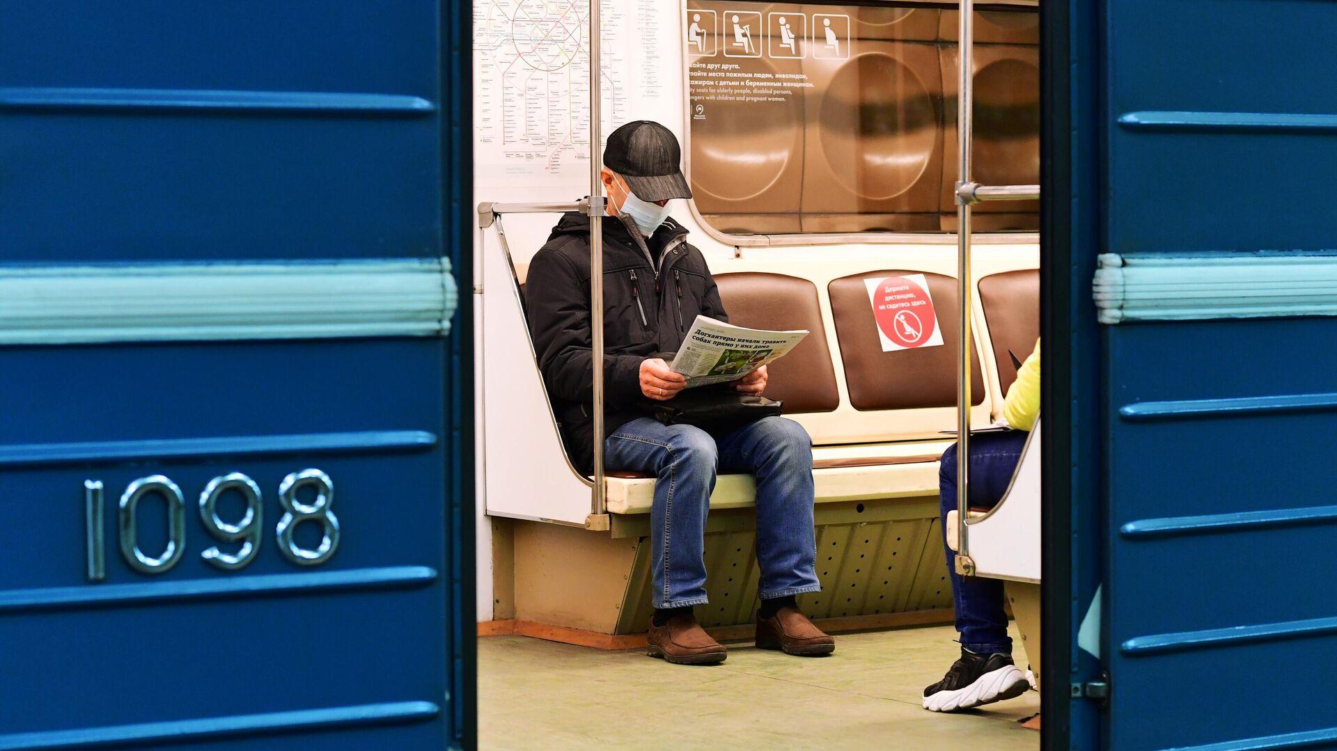 Пассажир в медицинской маске в вагоне поезда на станции метро Марьино Московского метрополитена - РИА Новости, 1920, 30.10.2020