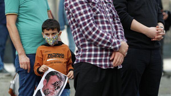 Мальчик держит плакат с изображением президента Франции Эммануэля Макрона во время акции протеста против Франции в Стамбуле, Турция