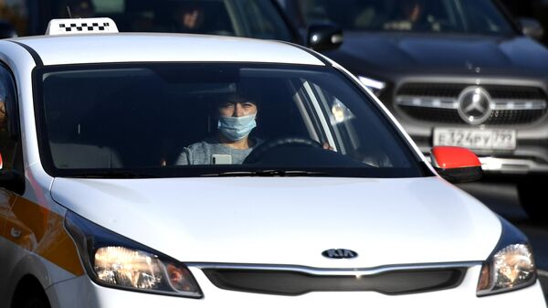 Водитель в защитной маске за рулем такси на одной из улиц в Москве