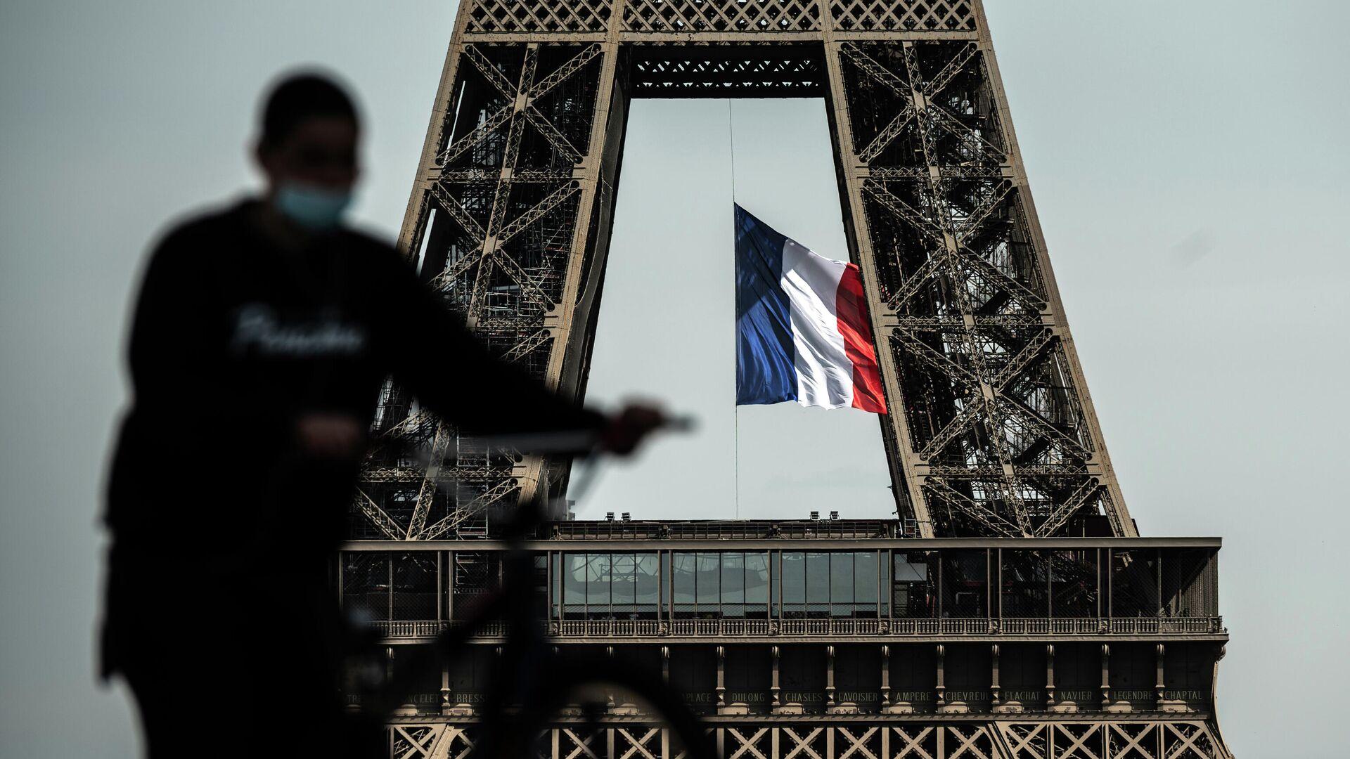 Мужчина проезжает мимо Эйфелевой башни в Париже  - РИА Новости, 1920, 29.10.2020