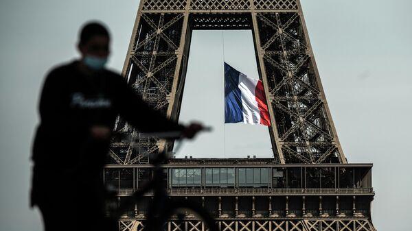 Мужчина проезжает мимо Эйфелевой башни в Париже