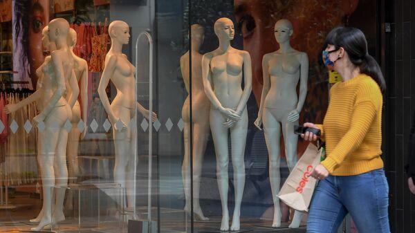 Женщина проходит мимо витрины с манекенами в Мельбурне, Австралия