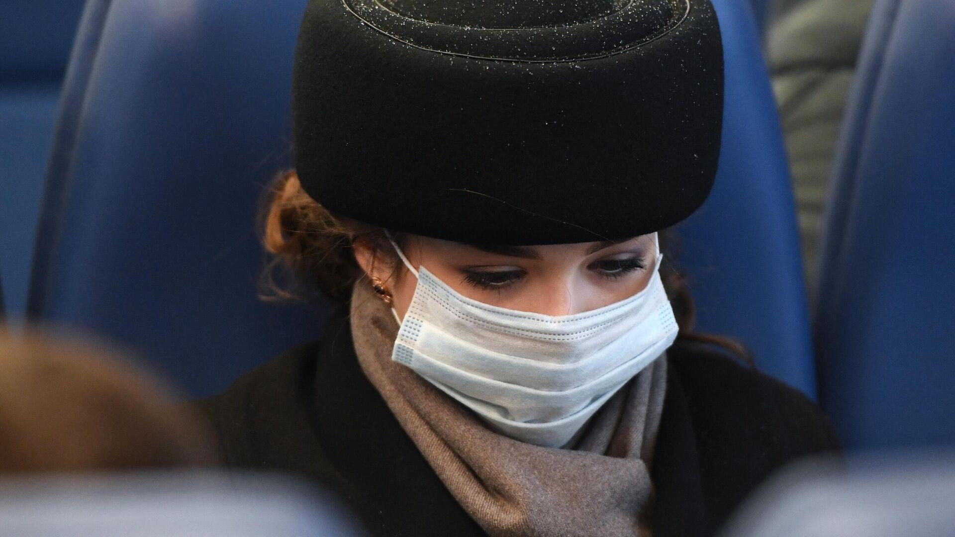 Девушка в медицинской маске в пригородном электропоезде в Новосибирске - РИА Новости, 1920, 13.11.2020