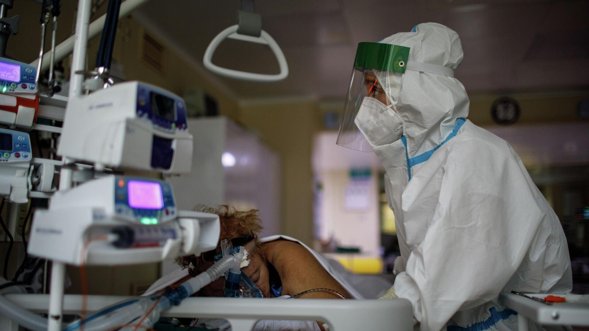 Медицинский работник оказывает помощь пациенту с COVID-19 в отделении реанимации и интенсивной терапии городской клинической больницы № 52 - РИА Новости, 1920, 02.11.2020