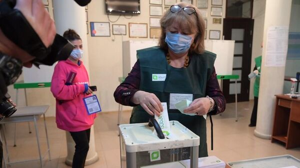 Женщина принимает участие в голосовании на парламентских выборах в Грузии на одном из избирательных участков в Тбилиси