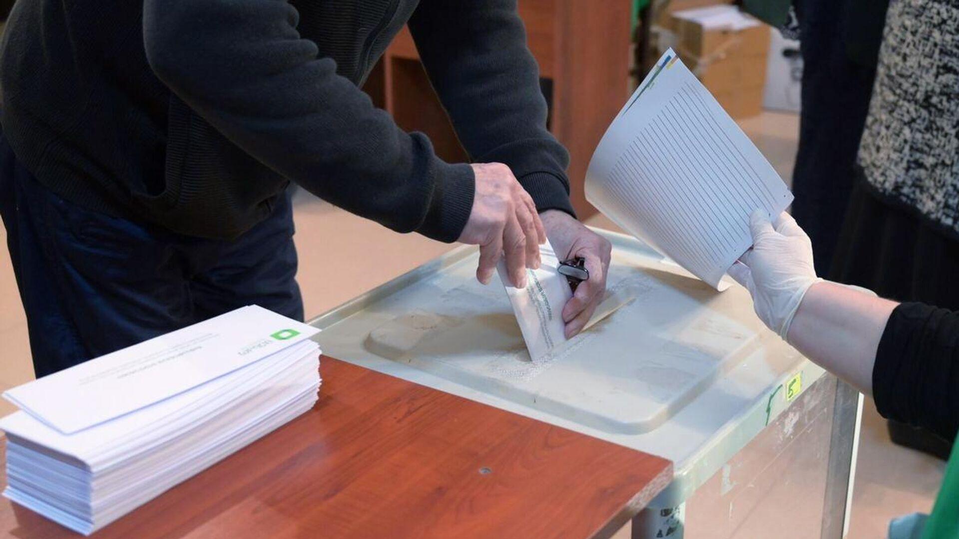 Мужчина принимает участие в голосовании на парламентских выборах в Грузии на одном из избирательных участков в Тбилиси - РИА Новости, 1920, 31.10.2020