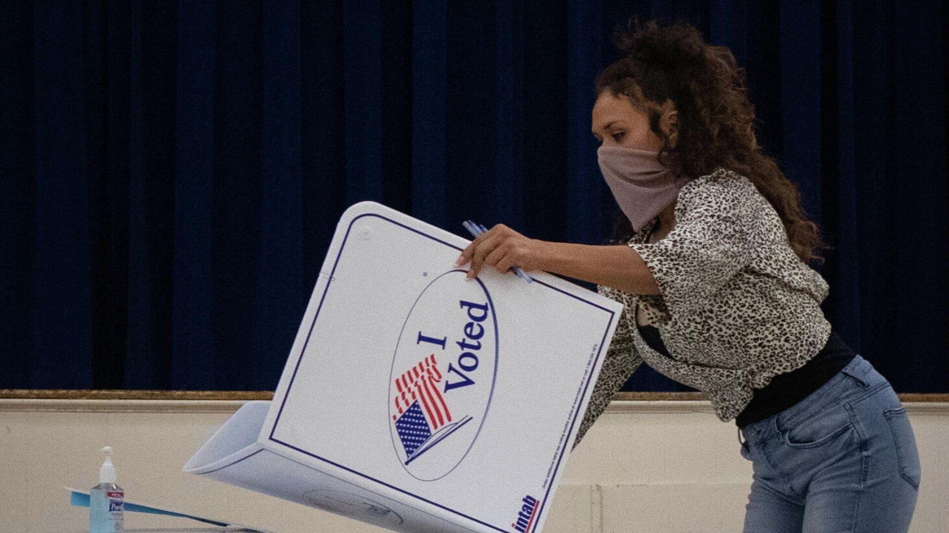 Сотрудница избирательной комиссии после окончания голосования на президентских выборах в США - РИА Новости, 1920, 02.12.2020