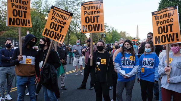 Люди с плакатами у Белого дома в Вашингтоне в день президентских выборов в США