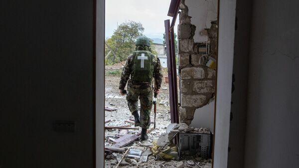 Военнослужащий возле дома, поврежденного в результате обстрела Степанакерта