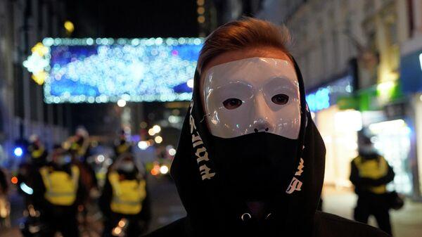 Участник Марша миллиона масок на Оксфорд-стрит в Лондоне