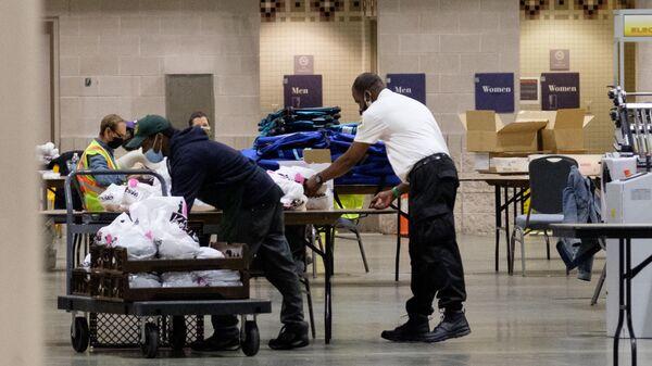Рабочие перевозят коробки с бюллетенями внутри Конгресс-центра в Филадельфии