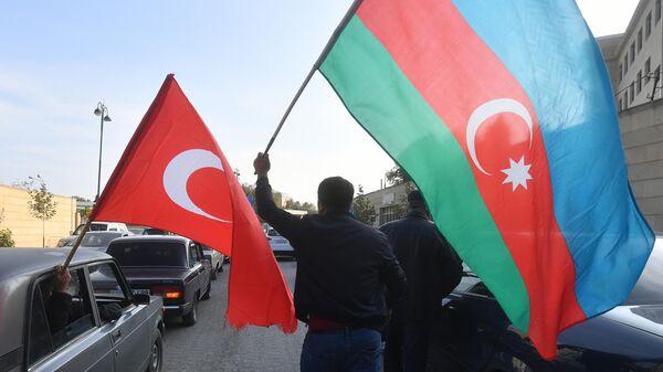 Люди с флагами Турции и Азербайджана в Баку