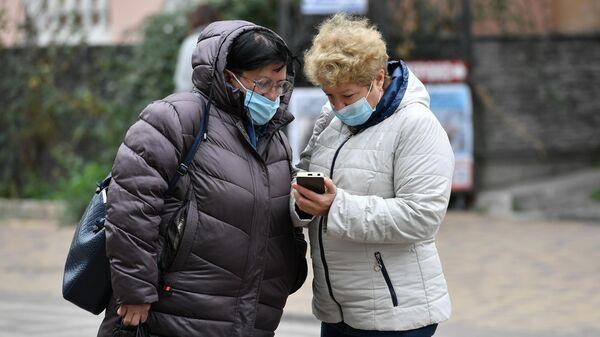 Женщины в медицинских масках на одной из улиц в Симферополе