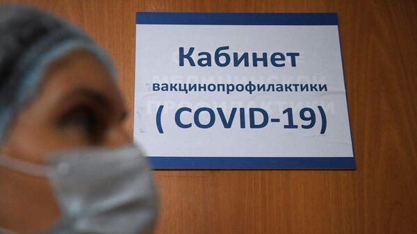 Медицинский работник у кабинета вакцинопрофилактики
