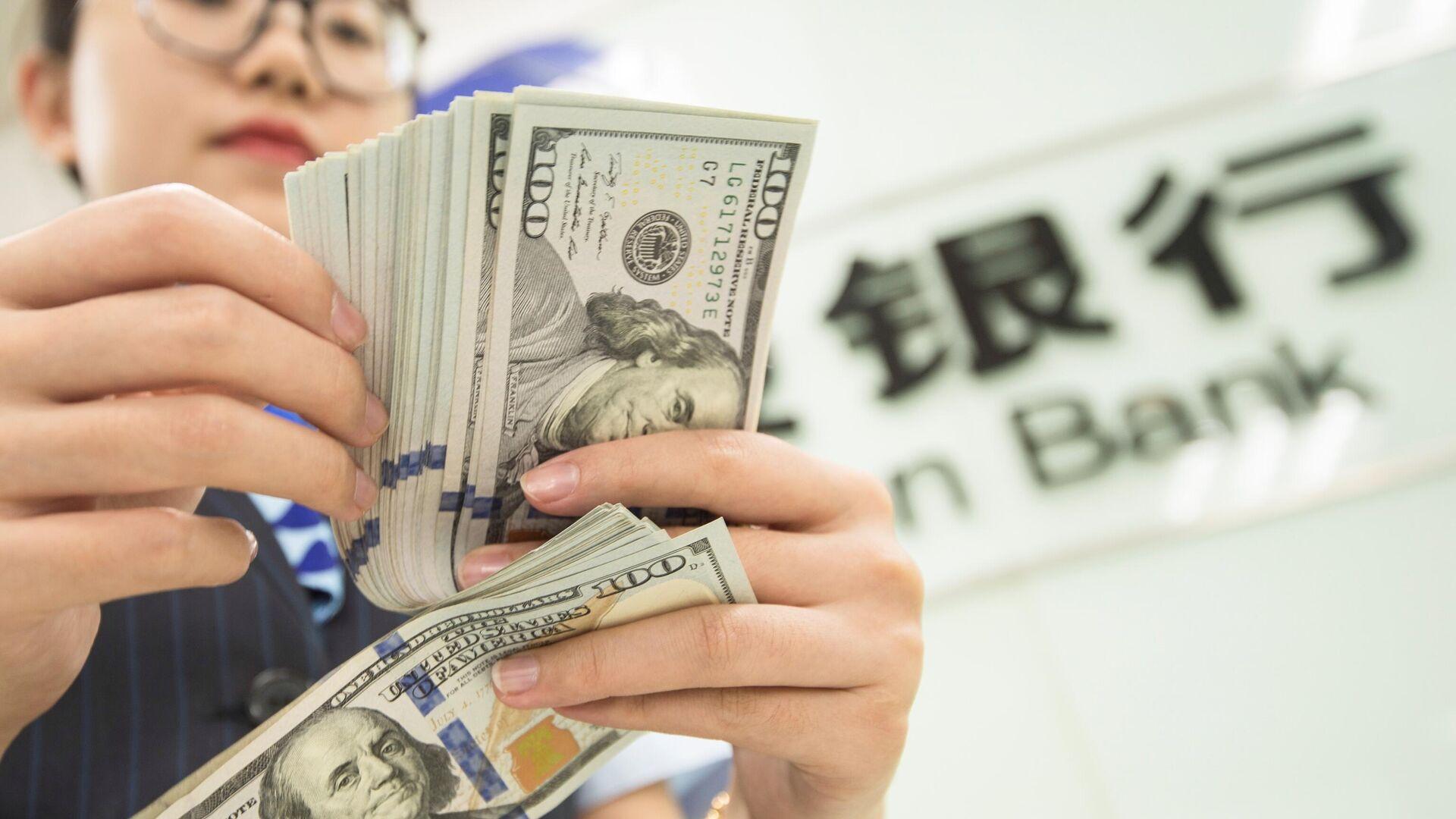 Банковский служащий пересчитывает доллары в Наньтуне, Китай  - РИА Новости, 1920, 12.11.2020