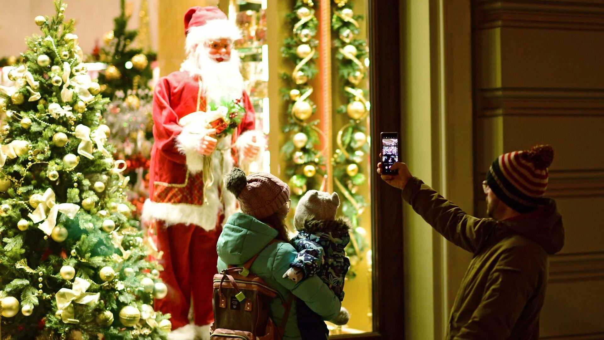 Прохожие фотографируют Санта Клауса в витрине на Никольской улице в Москве - РИА Новости, 1920, 14.11.2020