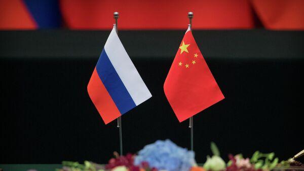 Государственные флаги России и Китая на столе в Доме народных собраний в Пекине