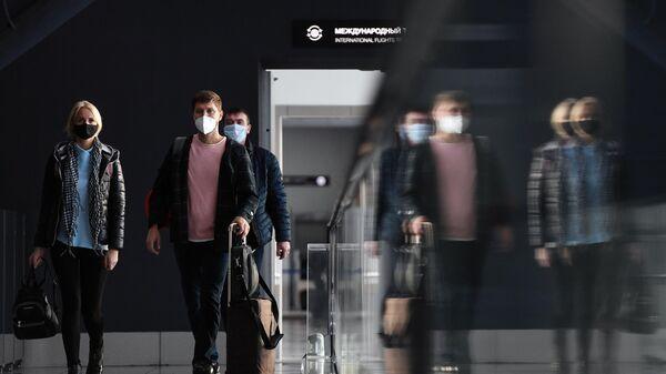 Пассажиры в защитных масках в международном аэропорту Толмачёво в Новосибирске