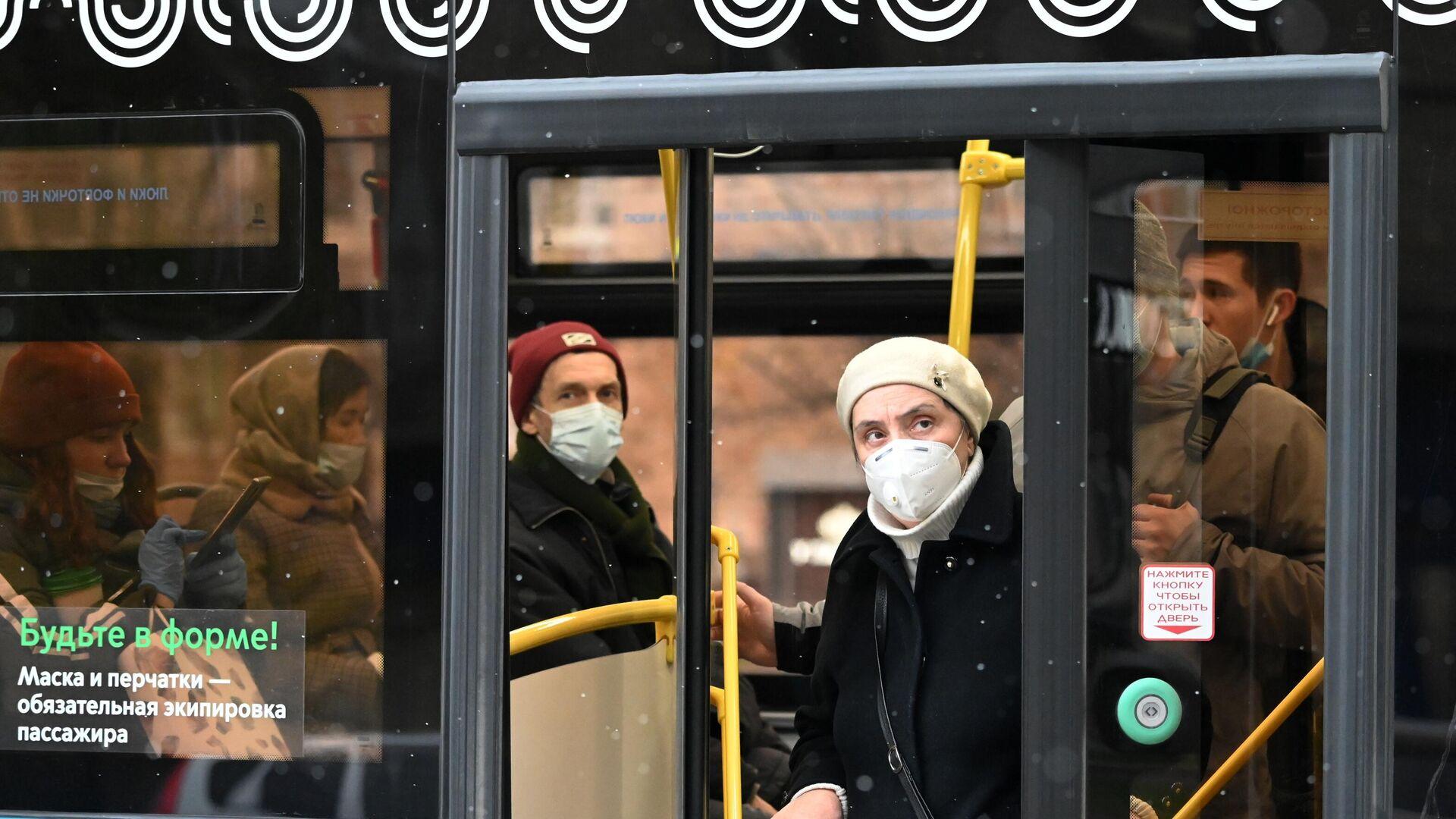 Люди в защитных масках на остановке общественного транспорта на Ленинском проспекте в Москве - РИА Новости, 1920, 17.11.2020