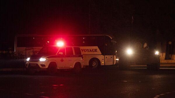 Бронемашина миротворцев и полицейская машина сопровождают автобусы с беженцами из Нагорного Карабаха, вернувшимися в Степанакерт из Еревана
