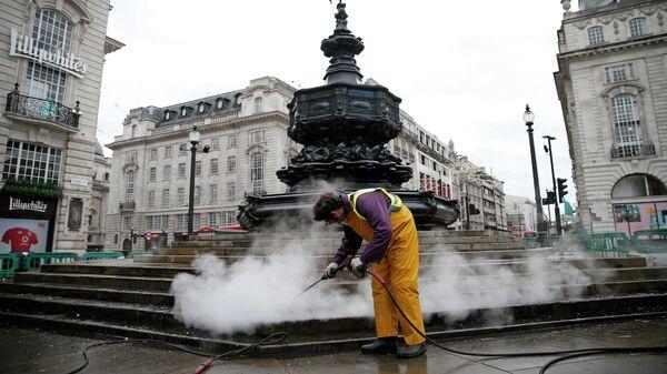 Рабочий чистит ступеньки, ведущие к Мемориальному фонтану Шафтсбери на площади Пикадилли в центре Лондона