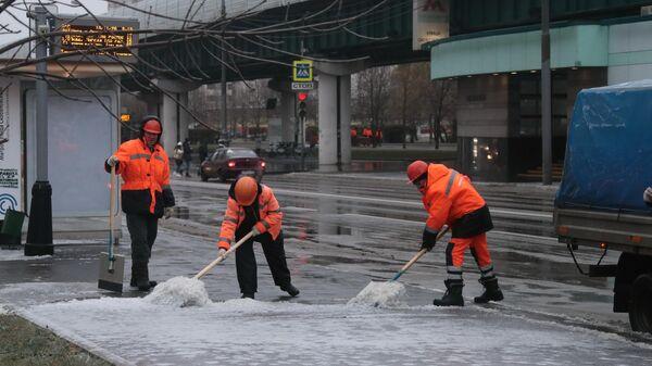 Работники коммунальных служб убирают улицу в Южном Бутово в Москве после прошедшего ледяного дождя