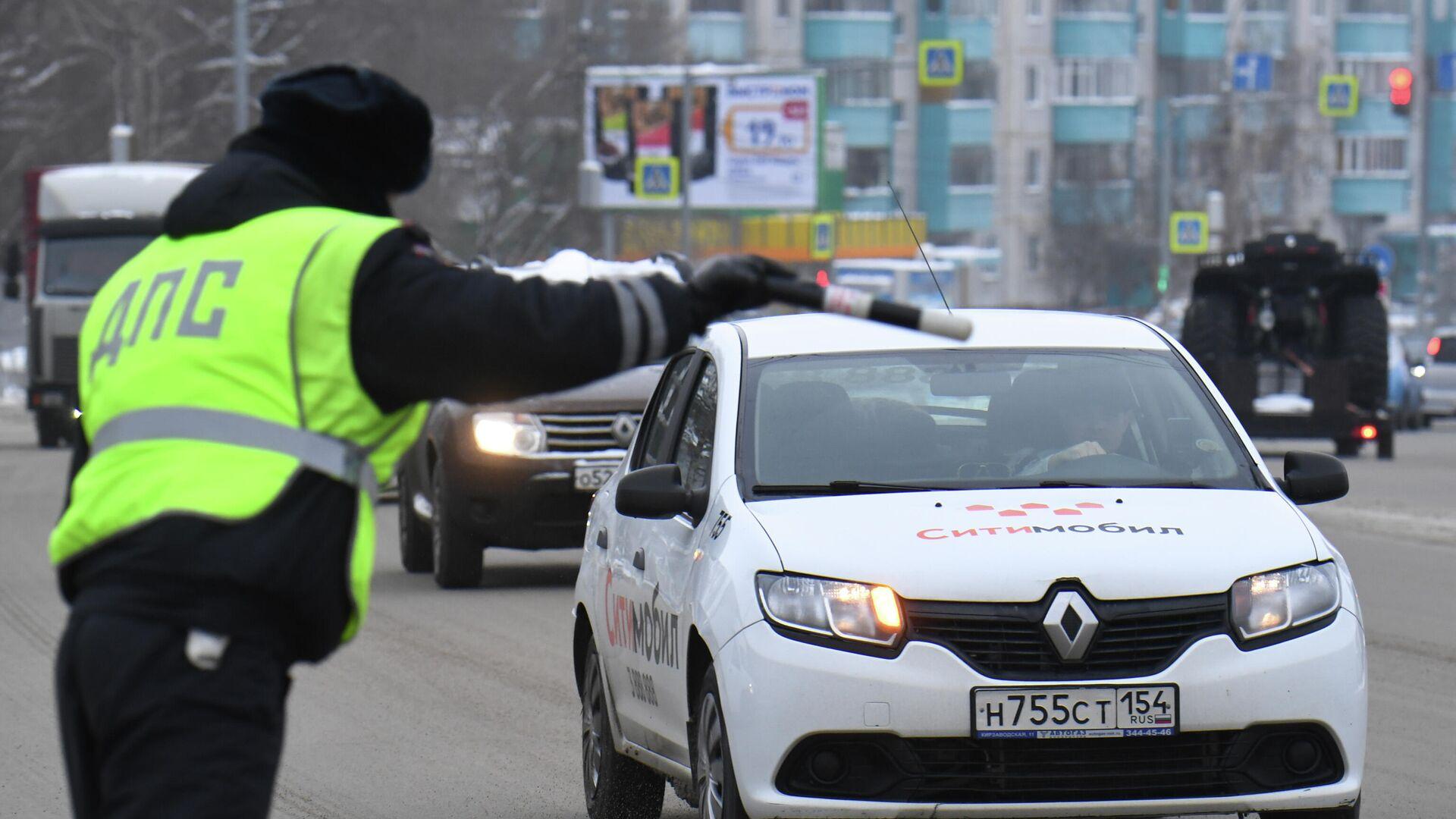 Сотрудник ДПС ГИБДД во время проверки соблюдения масочного режима водителями такси в Новосибирске - РИА Новости, 1920, 10.01.2021