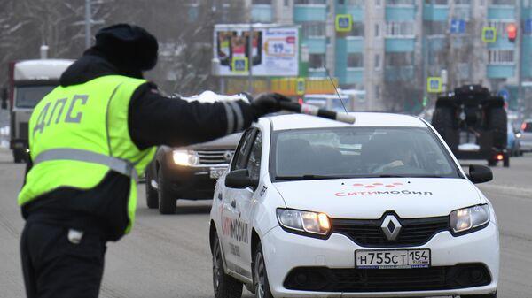 Сотрудник ДПС ГИБДД во время проверки соблюдения масочного режима водителями такси в Новосибирске