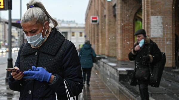 Женщина в защитной маске на улице в Москве