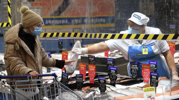 Покупатель и продавец в рыбном отделе гипермаркета Лента в период пандемии коронавируса в Новосибирске