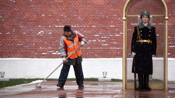 Мужчина убирает снег у Могилы Неизвестного Солдата у стен Московского Кремля