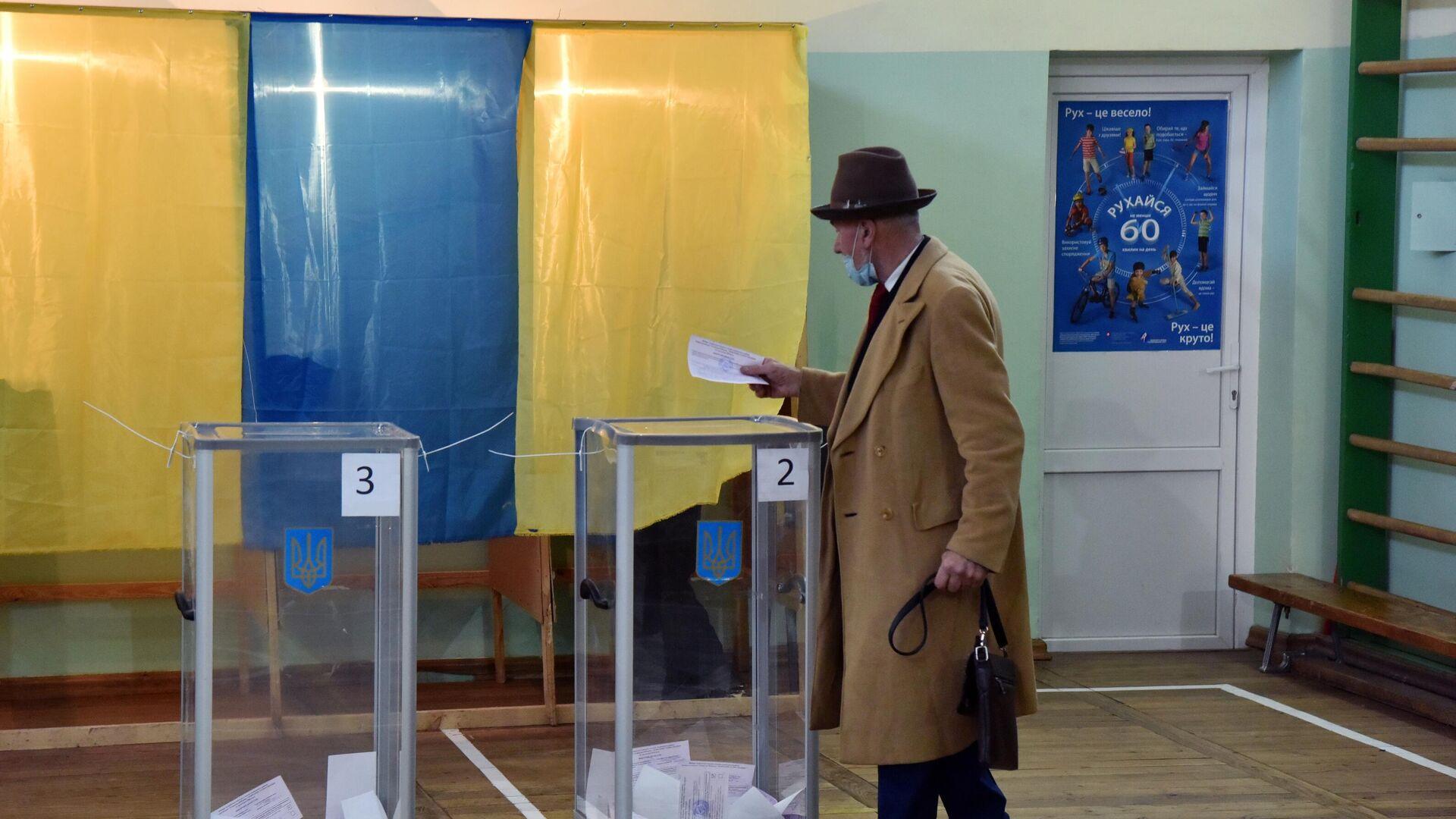 Мужчина голосует на избирательном участке во Львове - РИА Новости, 1920, 14.05.2021