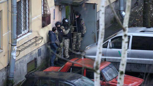 Сотрудники правоохранительных органов у жилого дома в городе Колпино Ленинградской области, где мужчина держит в заложниках детей в квартире